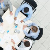 stock-photo-top-view-of-successful-business-people-sitting-at-a-table-for-meeting-with-copyspace